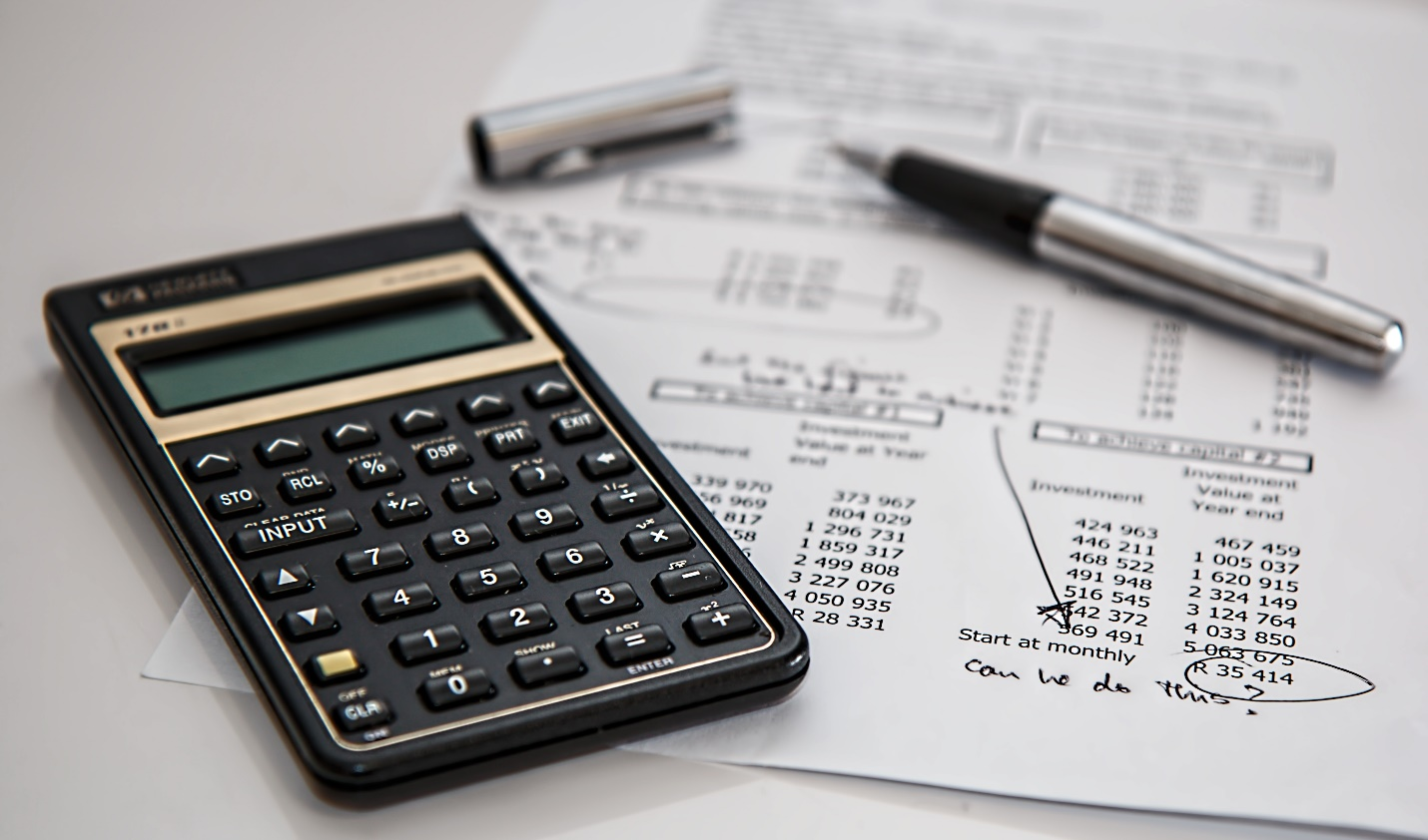 A calculator and pen on top of papers  Description automatically generated with medium confidence